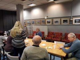 A kőbányai klubon a tagok figyelik egy asztal mellett a Láthatár Bolt bemutatóját