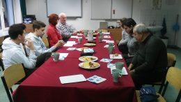 a képen a tagok az asztal körül űlnek