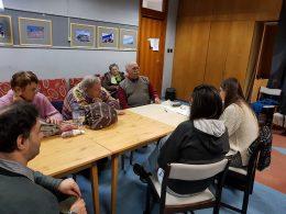 A tagok asztal körül ülve hallgatják az előadást