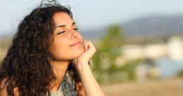 Egy nő egy napos parkban ül és örül a napfénynek