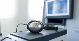 A képen egy repülőgép ülésénél elhelyezett monitor látható, fejhallgatóval