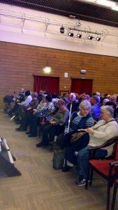 A tagok a színházterem elején ülve hallgatják az előadókat