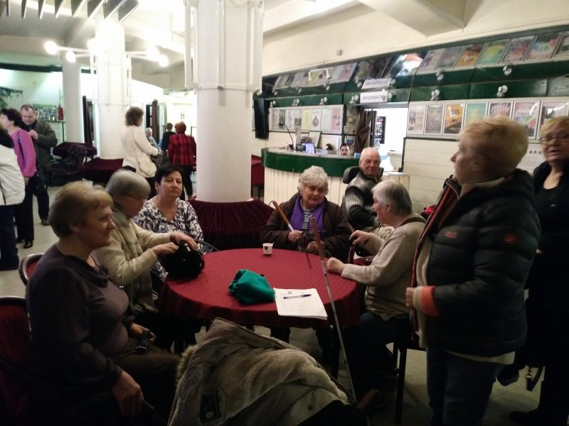 A színházterem előterében egy asztal mellett beszélgetnek az újpesti tagok