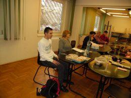 A képen a klub tagjai Zsuzsa bemutatóját hallgatják egy asztal körül ülve