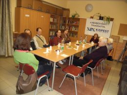 A képen az látható, ahogyan Koós Andrea a kispesti tagokhoz beszél egy asztal mellett ülve