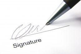 A képen egy toll látható, amint valaki aláírja vele a nevét