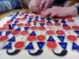 A játéktér egy tábla, faszínű, piros és kék mezőkkel