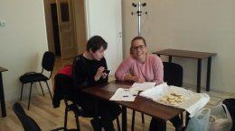 A képen az egyik tag beszélget egy asztal mellett ülve Verával, a kerületi szervezővel
