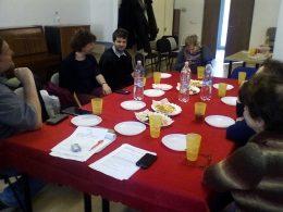 Az asztal mellett ülő klubtagok beszélgetnek és közben üdítőt isznak