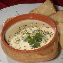 A képen egy tányérnyi sajtos zöldségkrémleves látható