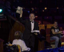 Fekete Péter magasba emeli a könyv egy példányát a cirkusz közönsége előtt