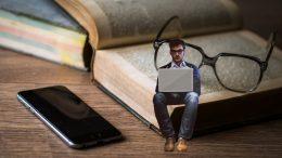 A képen egy férfi látható, amint a laptopján verset írva egy hatalmas régi könyv oldalain ül, a könyv mellett mobiltelefon, a férfi mögött szemüveg; a kép azt próbálja kifejezni, hogy a jelen alkotásai a régi alkotások vállán állva születnek meg