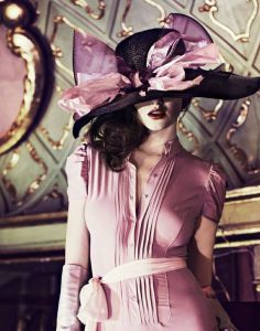 A képen egy szépen felöltözött hölgy látható, elegáns kalapban