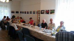 A rákosmenti klubnapon egy asztal körül ülve hallgatják a tagok a fogyasztóvédelmi tájékoztatót