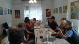 A rákosmenti klubtagok egy asztal körül ülve hallgatják a Braille-írásról az előadást