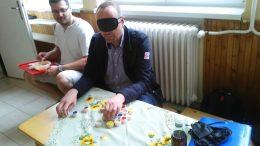 Az egyik vendég egy érzékenyítős játékot próbál ki a családi napon a Piroska Óvodában