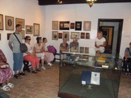 A kispesti klubkirándulás résztvevői a múzeumi tárlatvezetést hallgatják a múzeum egyik kiállítótermében
