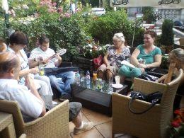 A képen a beszélgetés egy pillanata látható, a tagok egy étterem székein ülnek