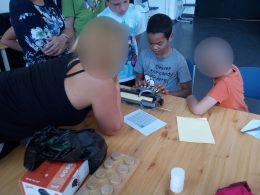 A diákok a Braille-írógépet próbálják ki Andi segítségével