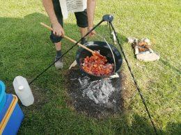 A képen a bogrács látható, amint az egyik szakács kevergeti