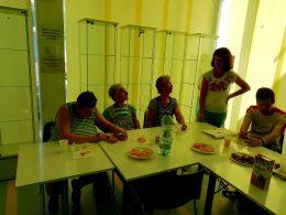 Koós Andrea tart előadást a zuglói klubnapon, a tagok ülve hallgatják egy asztal körül ülve