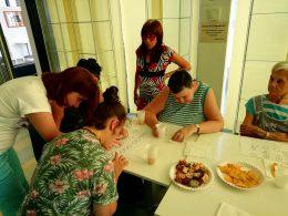 Andrea a Braille-írást mutatja egy zuglói klubtagnak