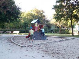 A képen egy modern csúszda látható, mely körül négy kisgyerek játszik