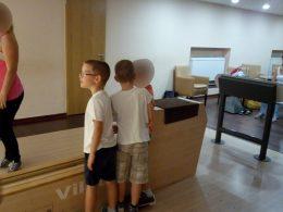 A képen három bowlingozó gyerek néz egy bowlingozó felnőttet, hogy ellessék a dobástechnikáját