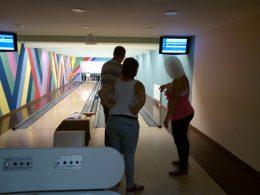 A képen szülők figyelik a gyerekek játékát a bowling pályák mögött