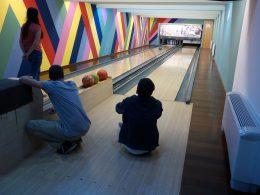Egy tag gurítja a bowling-golyót, másik kettő pedig a pályához közel ülve nézi