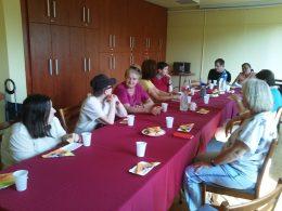 A békási klubtagok az ügyfélszolgálat előadását hallgatják egy asztal mellett ülve