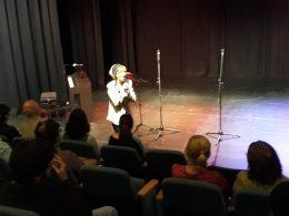 A közönség hallgatja az egyik énekesnőt, aki egy színpadon ülve énekel Terézvárosban