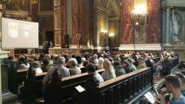 A képen a hallgatóság látható a Bazilikában, amint a padokban ülnek