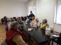 A körzeti megbízott beszél az újpesti klub tagjainak, akik egy asztalnál ülve hallgatják őt