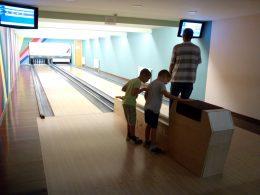 Két kisgyerek nézegeti a bowling golyókat az angyalföldi biwling napon