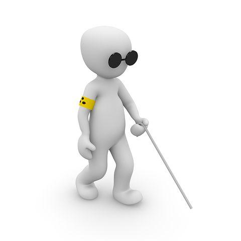 A képen egy napszemüveges, fehér bottal sétáló bábu látható