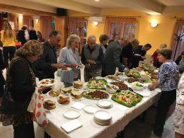 A képen a rákosmenti ünnepi rendezvényt követő fogadás látható, ahol a vendégek ételt választanak maguknak
