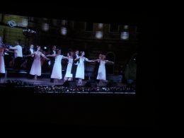 részlet a vetítésből, táncospárok láthatók, nők fehérben, férfiak feketében