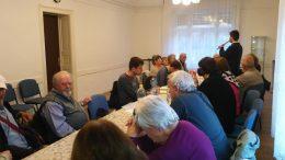 A rákosmenti klubtagok egy asztal köré ülve hallgatják az ügyfélszolgálat előadását