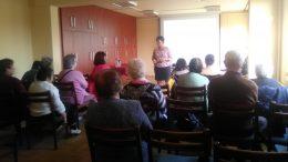 Az AKKU Egyesület munkatársa tart előadást a békásmegyeri klubtagoknak, akik ülve hallgatják őt