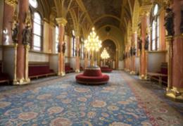 A képen a parlament belső része látható, elegáns kárpitozású székekkel
