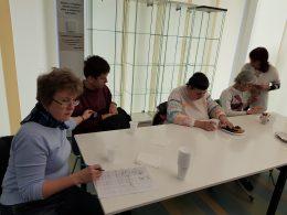 A zuglói klub tagjai egy asztal mellett ülve hallgatják Kiss Mártát
