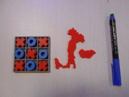A képen néhány kinyomtatott tárgy látható, mint egy amőba játék, egy Olaszország és egy Magyarország alakzat