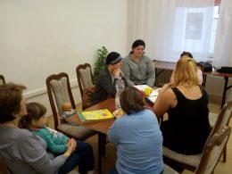 A Fecske Szolgálat beszél az angyalföldi klubnapon a tagoknak, akik egy asztal körül ülnek