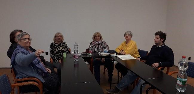 A fotó Újpesten, a lámpás klubon készült. Az asztalnál a klubtagok ülnek és beszélgetnek.