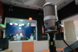 A fotó előterében mikrofon, a hátterében egy stúdió képe látható.