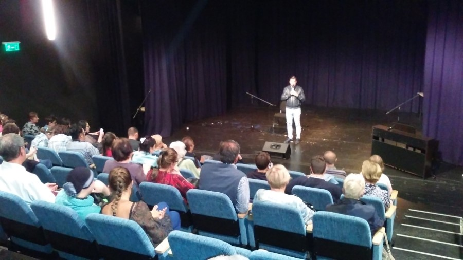 A közönség a nézőtéren ülve hallgatja Kökény Attilát.
