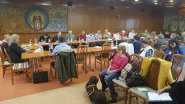 A képen oldalról látszódnak az asztalok körül és a széksorokban ülő képviselők.