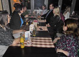 Jobb oldalon középen, szőke hajjal Lengyel Zsófia, mellette fekete öltönyben Németh Dávid ülnek az asztalnál, mellettük és szemben a klub többi résztvevője látható.