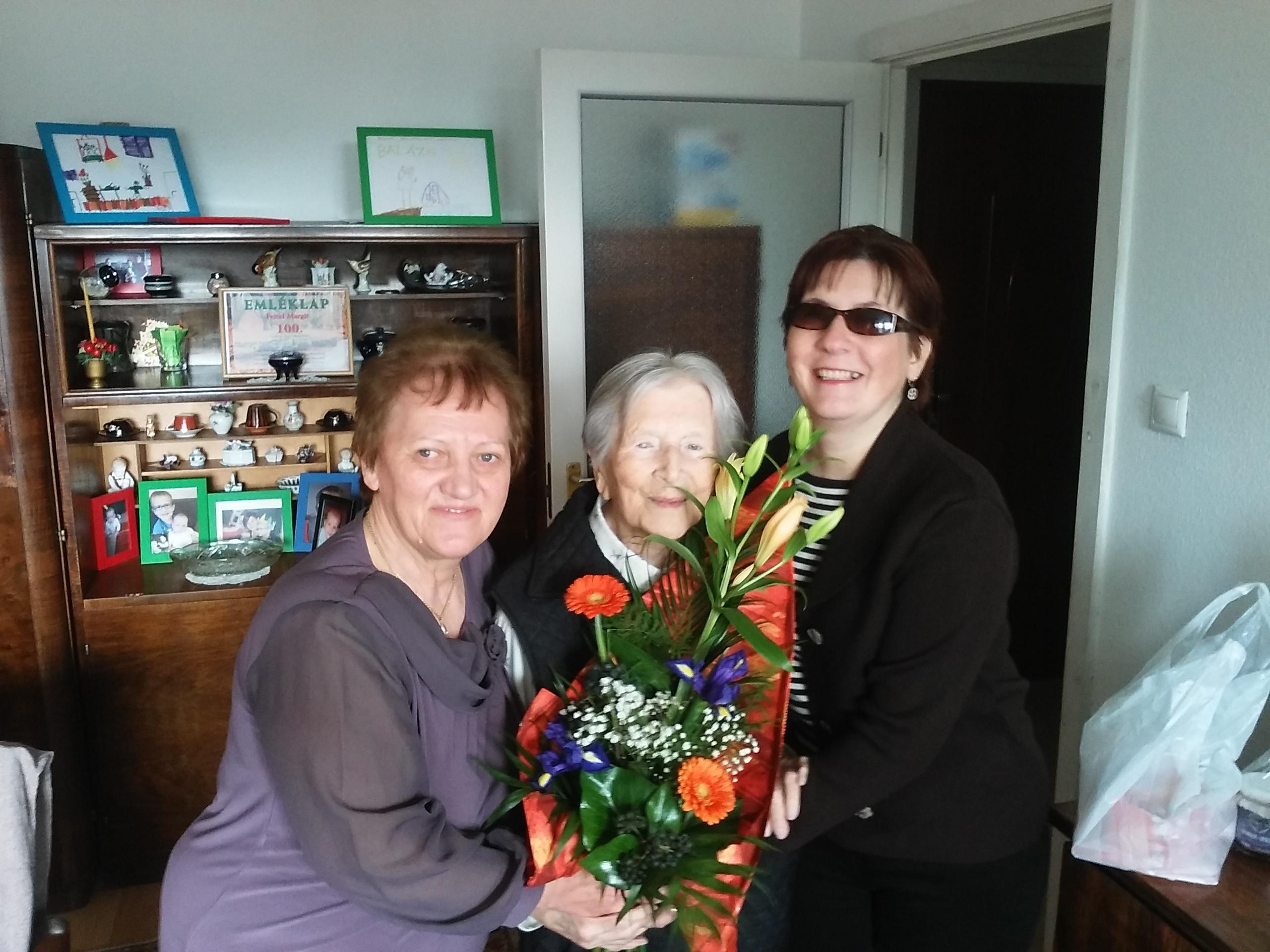 A képen középen a 104 éves ünnepelt, Margitka néni látható virággal a kezében. Mellette jobbról Fodor Ágnes elnök, balról Vasné Pintér Teréz közösségi civilszervező.